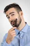 Schließen Sie herauf Porträt des jungen bärtigen Mannes, der seinen Bart kämmt, der Kamera betrachtet Stockfoto
