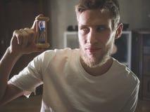 Schließen Sie herauf Porträt des jungen bärtigen Mannes in der zufälligen netten Haltezeit-Sandsanduhr zu Hause stockbild