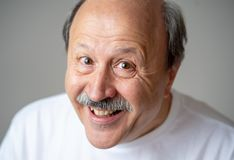 Schließen Sie herauf Porträt des lächelnden älteren Mannes mit dem glücklichen Gesicht, welches die Kamera betrachtet stockfoto
