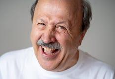 Schließen Sie herauf Porträt des lächelnden älteren Mannes mit dem glücklichen Gesicht, welches die Kamera betrachtet lizenzfreies stockfoto