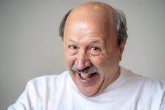 Schließen Sie herauf Porträt des lächelnden älteren Mannes mit dem glücklichen Gesicht, welches die Kamera betrachtet lizenzfreies stockbild