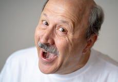 Schließen Sie herauf Porträt des lächelnden älteren Mannes mit dem glücklichen Gesicht, welches die Kamera betrachtet stockfotografie