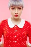 Schließen Sie herauf Porträt des schönen dollish Mädchens mit dem kurzen hellvioletten Haar, das rotes Kleid über rosa Hintergrun Lizenzfreie Stockfotografie