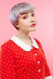 Schließen Sie herauf Porträt des schönen dollish Mädchens mit dem kurzen hellvioletten Haar, das rotes Kleid über rosa Hintergrun Stockbild