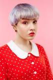 Schließen Sie herauf Porträt des schönen dollish Mädchens mit dem kurzen hellvioletten Haar, das rotes Kleid über rosa Hintergrun Lizenzfreies Stockbild
