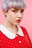Schließen Sie herauf Porträt des schönen dollish Mädchens mit dem kurzen hellvioletten Haar, das rotes Kleid über rosa Hintergrun Lizenzfreie Stockfotos