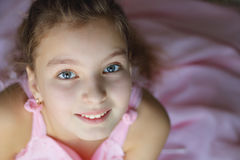 Schließen Sie herauf Porträt des schönen jugendlich Mädchens im rosa Kleid enthusiastisch mit einem Lächeln, welches die Kamera b Stockbild