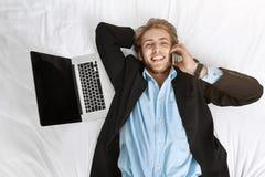 Schließen Sie herauf Porträt des schönen jungen Geschäftsmannes, der im Bett mit Laptop liegt und am Telefon sprechen und mit in  Stockfotos
