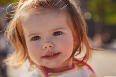 Schließen Sie herauf Porträt des schönen kleinen Babys, blondes kleines Mädchen im bunten Pullover im Park draußen Lizenzfreie Stockbilder