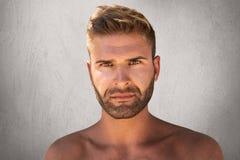 Schließen Sie herauf Porträt des schönen Mannes mit den dunklen Augen, Borste und modischer Frisur, die nackt ist und mit ernstem Lizenzfreie Stockfotografie