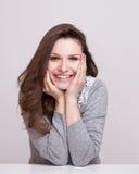 Schließen Sie herauf Porträt einer glücklichen lächelnden Frau, die ihr Kinn auf ihren Händen stillsteht und direkt der Kamera be Stockfotografie