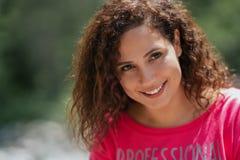 Schließen Sie herauf Porträt einer netten gelockten jungen Frau, die draußen lächelt stockbilder