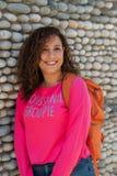 Schließen Sie herauf Porträt einer netten gelockten jungen Hochschulstudentfrau, die draußen lächelt stockfotografie