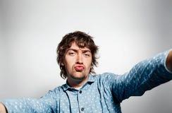 Schließen Sie herauf Porträt eines jungen küssenden Mannes, der a hält Stockbild