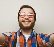 Schließen Sie herauf Porträt eines netten bärtigen Mannes, der selfie über weißem Hintergrund nimmt Stockfoto