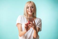 Schließen Sie herauf Porträt stilvoller blonder Dame, die ihren Handy hält Stockfotografie