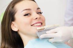 Schließen Sie herauf Porträt von jungen Frauen im Zahnarztstuhl, überprüfen Sie und wählen Sie die Farbe der Zähne vor Zahnarzt m stockbilder