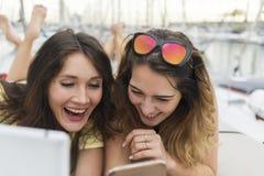 Schließen Sie herauf Porträt von zwei aufgeregten Freundinnen mit den Handys, die sich hinlegen und in camera lachen und schauen lizenzfreies stockfoto
