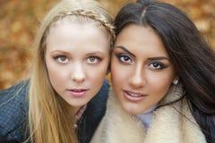 Schließen Sie herauf Porträt von zwei schönen jungen Frauen auf dem Hintergrund Stockfoto