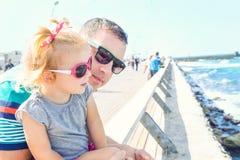 Schließen Sie herauf Porträts des Vaters und der kleinen Tochter in der Sonnenbrille, die zum Meer auf der Seeseite von Tel Aviv  stockfotografie