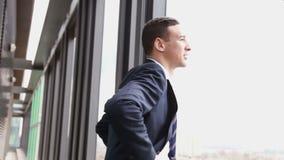 Schließen Sie herauf Profil des lächelnden bereitstehenden Fensters des Geschäftsmannes mit Stadtansicht stock video