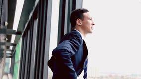 Schließen Sie herauf Profil des lächelnden bereitstehenden Fensters des Geschäftsmannes mit Stadtansicht stock video footage