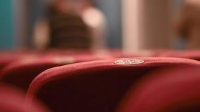 Schließen Sie herauf Rückenlehne rote Sitze in einem Konzertsaal mit einem Nummernschild und Leuten im Hintergrund stock video footage