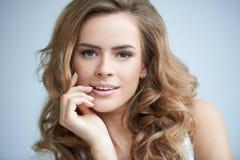 Schließen Sie herauf recht gelockte junge Frauen-Hand auf Gesicht Stockfotos