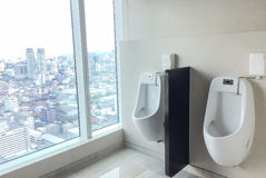 Schließen Sie herauf Reihe von Innentoiletten-Männern öffentliche Toilette, Toilette Weiße keramische Toiletten mit Kurven-modern Lizenzfreies Stockbild