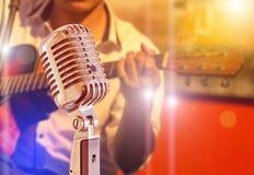 Schließen Sie herauf Retro- Mikrofon mit dem Musiker, der Akustikgitarre auf Band im Nachtkonzert spielt Lizenzfreies Stockbild
