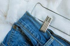 Schließen Sie herauf rostfreie Wäscheklammer auf blauem Baumwollstoff Lizenzfreies Stockfoto