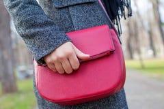 Schließen Sie herauf rote Tasche u. weibliche Hand Lizenzfreie Stockfotos