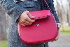 Schließen Sie herauf rote Tasche u. weibliche Hand Stockbild