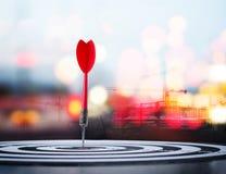 Schließen Sie herauf roten Pfeilpfeil des Schusses auf Mitte der Dartscheibe mit constru Stockfoto