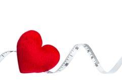Schließen Sie herauf rotes Herz mit dem messenden Band, lokalisiert auf weißem backgr Lizenzfreies Stockfoto