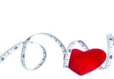 Schließen Sie herauf rotes Herz mit dem messenden Band, lokalisiert auf weißem Hintergrund Lizenzfreie Stockfotos
