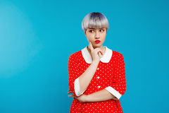Schließen Sie herauf schönes dollish Mädchen des Porträts mit dem kurzen hellvioletten Haar, das rotes Kleid über blauem Hintergr Stockfotos