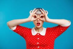 Schließen Sie herauf schönes dollish Mädchen des Porträts mit dem kurzen hellvioletten Haar, das rotes Kleid über blauem Hintergr Lizenzfreies Stockbild