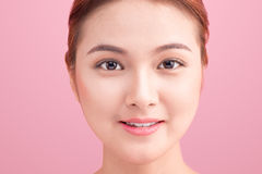 Schließen Sie herauf schönes Gesicht der jungen Frau auf Rosa Stockbild
