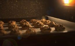 Schließen Sie herauf Schokoladensplitterplätzchen auf einem Backblech im Ofen, in gefiltertem rotem und braunem Weinlesebild, sel lizenzfreies stockbild