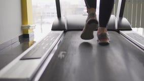 Schließen Sie herauf Schuss der Athlet ` s Füße, der entlang die Tretmühle geht stock video