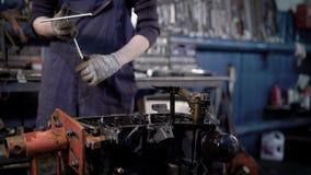 Schließen Sie herauf Schuss der Mann ` s Hände, der in der Reparaturwerkstatt arbeitet, die Mechanikerreparaturen das Teil des Au stock video footage