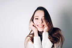 Schließen Sie herauf Schuss der stilvollen jungen Frau, die gegen weißen Hintergrund lächelt Schönes weibliches Modell, welches d Lizenzfreie Stockfotografie