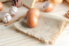 Schließen Sie herauf Schuss des braunen Eies auf Hanfsackleinen auf Holztisch Lizenzfreies Stockfoto