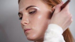 Schließen Sie herauf Schuss des Gesichtes einer Schönheit, die mit Make-up gemalt wird stock video