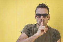 Schließen Sie herauf Schuss des hübschen Mannes mit shhh Geste lizenzfreie stockbilder