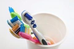 Schließen Sie herauf Schuss des Satzes mehrfarbiger Zahnbürsten im Glas auf Cl Lizenzfreies Stockfoto