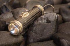 Schließen Sie herauf Schuss einer antiken ` s Taschenlampe 1920 im Kieselhintergrund Stockfotos