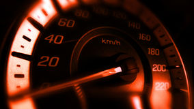 Schließen Sie herauf Schuss eines Geschwindigkeitsmeters in einem Auto mit orange Licht Stockfotos