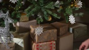 Schließen Sie herauf Schuss von ein Mann ` s Händen, der Kästen mit Geschenken unter einen verzierten Weihnachtsbaum setzt stock video